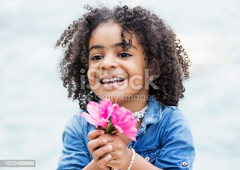A beautiful mixed race African-American and Hispanic girl, 3 years old, holding a pink flower, smiling.