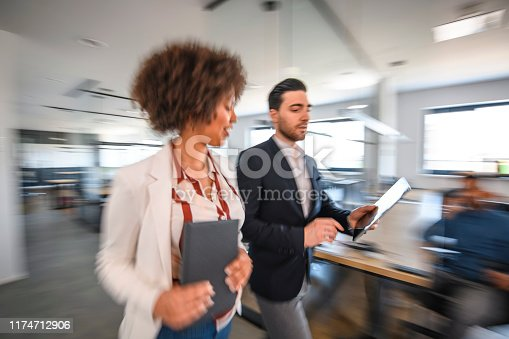 1163429625istockphoto Mixed Race and Caucasian Businesspeople Walking and Talking 1174712906
