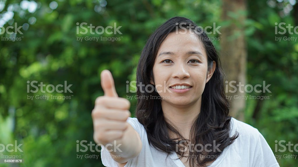 Mixed race Asian girl thumb up with nature background stock photo