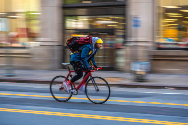 Mixed Race Bicycle Messenger Cycling on City Street stock photo
