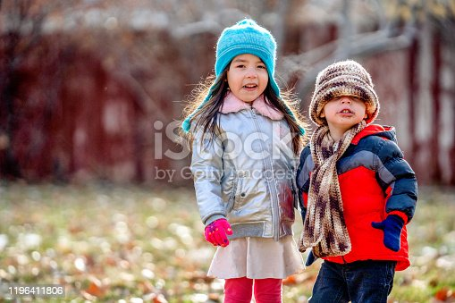 1051172208 istock photo Mixed Race Boy and Girl Smiling and Playing in her Backyard Dressed up Warmly for Winter Fun 1196411806