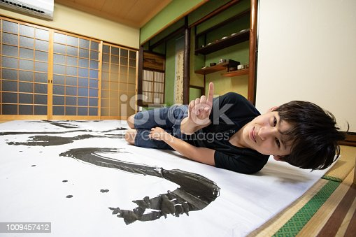 istock Mixed race boy enjoys Japanese calligraphy 1009457412