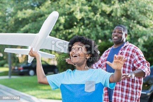 1091098220istockphoto Mixed race boy playing with toy plane, father behind 598077928