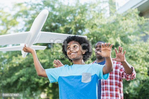 1091098220 istock photo Mixed race boy playing with toy plane, father behind 598537892