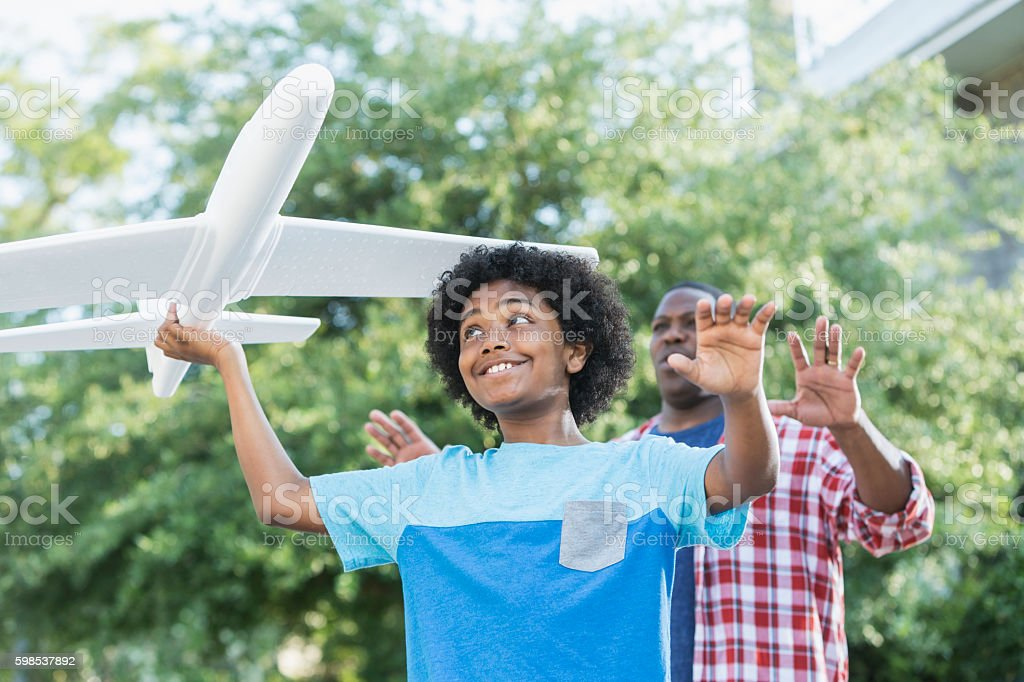 Mixed race boy playing with toy plane, father behind stock photo