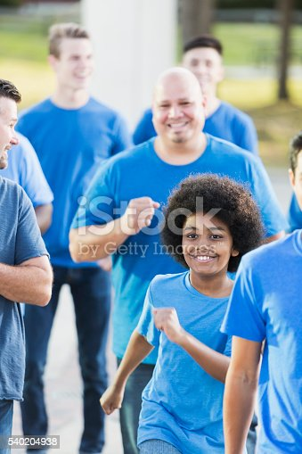 istock Mixed race boy running with a team of men 540204938