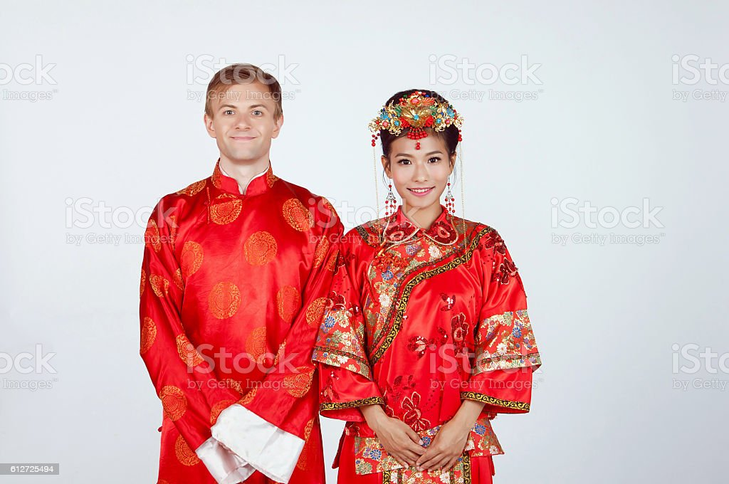 Mixed Race Bride and Groom wearing traditional Chinese wedding outfits stock photo