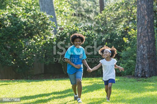 1091098220istockphoto Mixed race brother and sister running in park 598077958