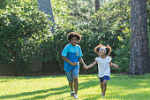 A 12 year old boy playing with his 7 year old sister in the park on a sunny day, holding her hand as they run across the grass, smiling. They are mixed race, part African American, Hispanic, Asian and Pacific Islander ethnicity.