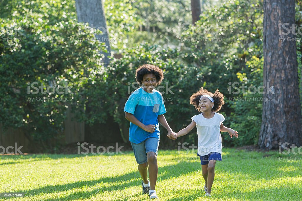 Mixed race brother and sister running in park stock photo