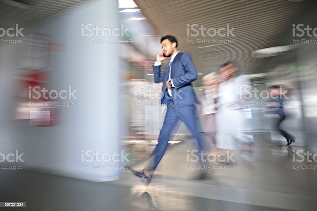 Mixed race businessman in busy workplace stock photo