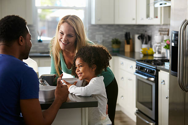 gemischt rennen paar und tochter reden zusammen in der küche - küche aus paletten stock-fotos und bilder