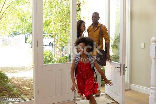 670900812 istock photo Mixed race couple and their daughter arriving at home 1253632079