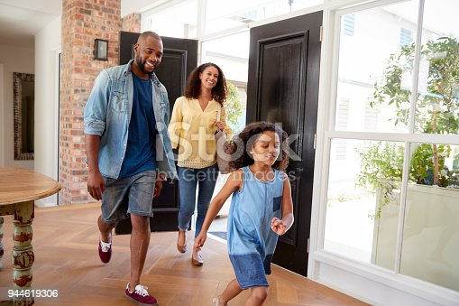 670900812 istock photo Mixed race couple and their daughter arriving home 944619306