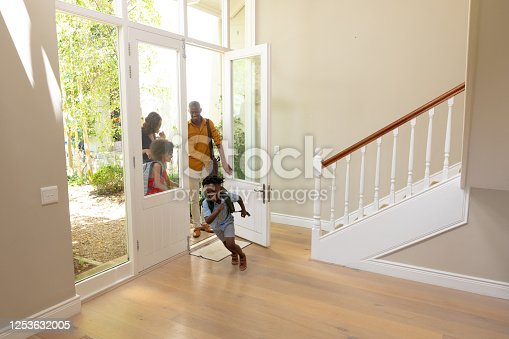670900812 istock photo Mixed race couple and their young son and daughter arriving at home 1253632005