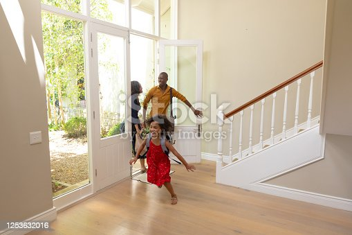 670900812 istock photo Mixed race couple and their young son and daughter arriving at home 1253632016