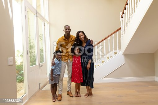 670900812 istock photo Mixed race couple and their young son and daughter standing in the hallway of their home 1253632024