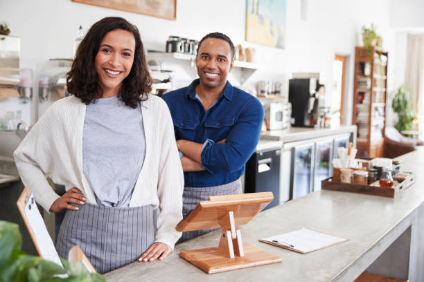 mixed race couple behind the counter at their coffee shop - owner stock pictures, royalty-free photos & images