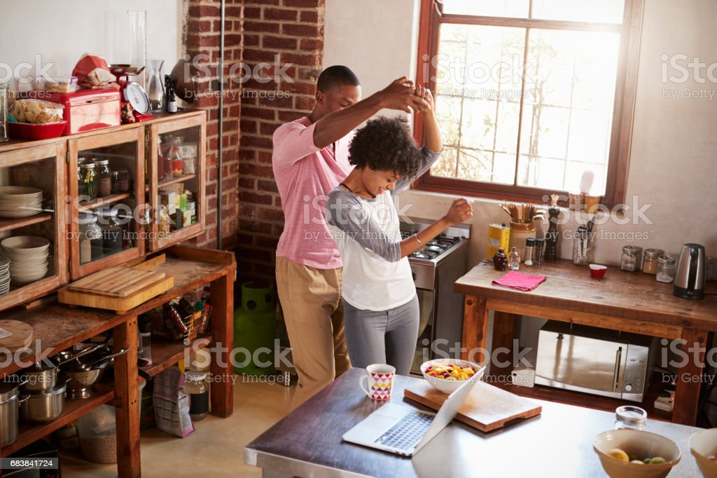 Mixed race couple dancing in kitchen, elevated view stock photo