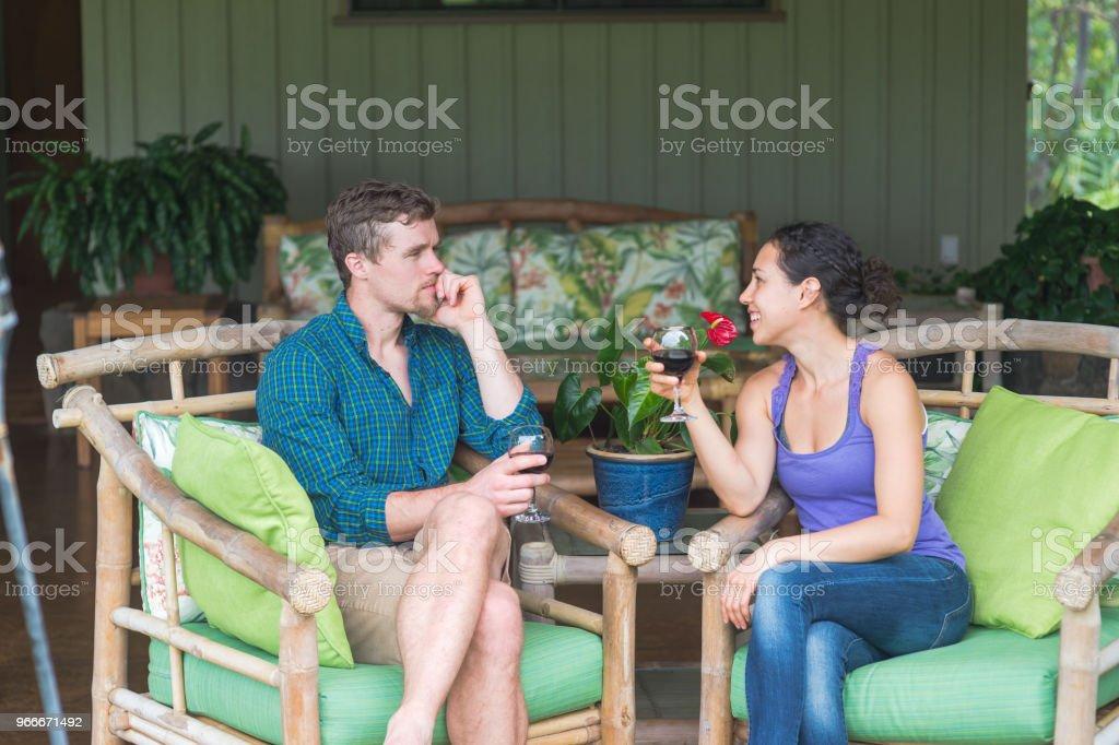 Mixed race couple drinking wine  on their honeymoon in Hawaii stock photo