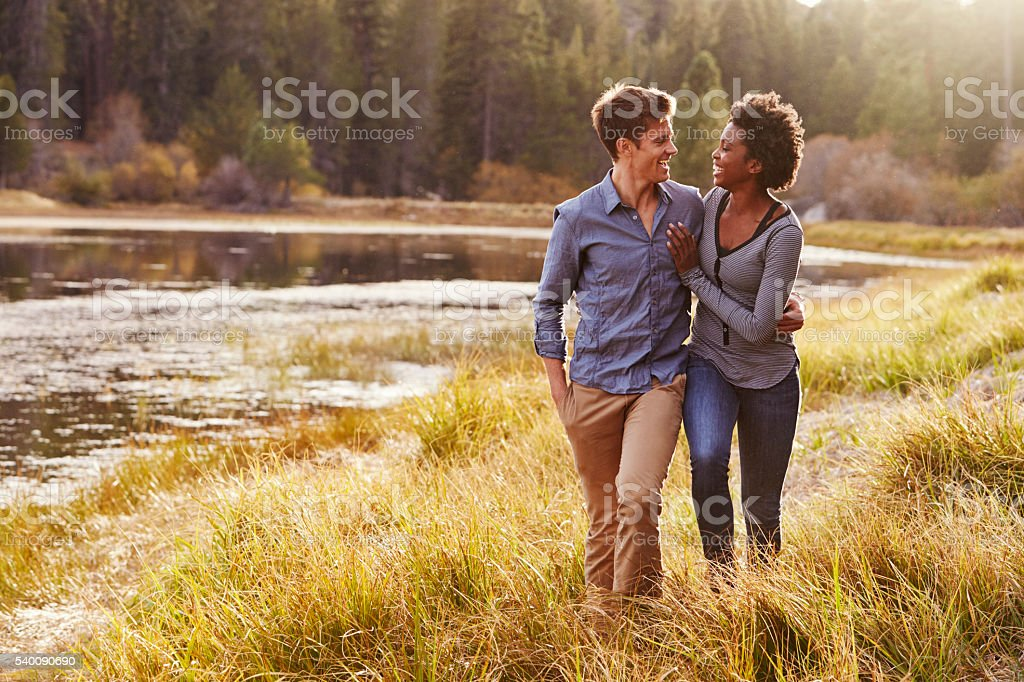 Mixed race couple embracing, walking near a rural lake stock photo