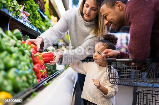 A pre-school age girl helps her parents pick out veggies in the produce section at the grocery store. She is reaching for a red pepper.
