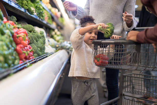 Mixed race couple grocery shopping with their preschool-age daughter stock photo