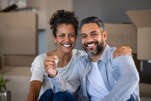 Middle aged multiethnic couple embracing and holding house keys with carboard boxes behind them. Cheerful couple sitting on floor in new home. Portrait of indian man and african woman showing house keys while looking at camera after relocation.