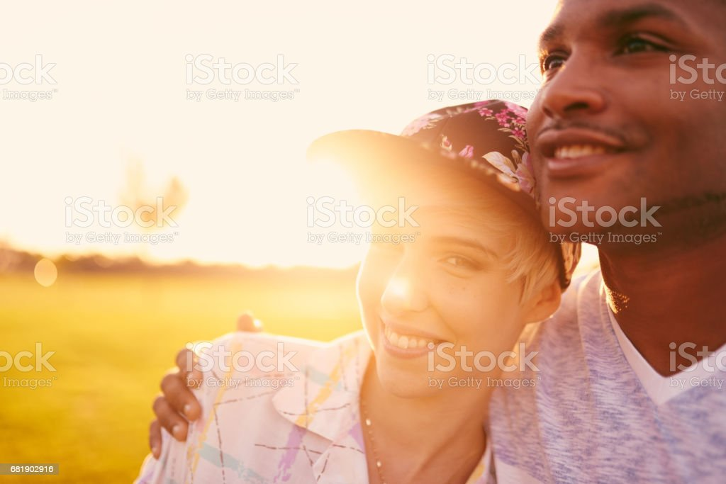 Mixed race couple of millennials in a grass field cuddling and showing affection together stock photo