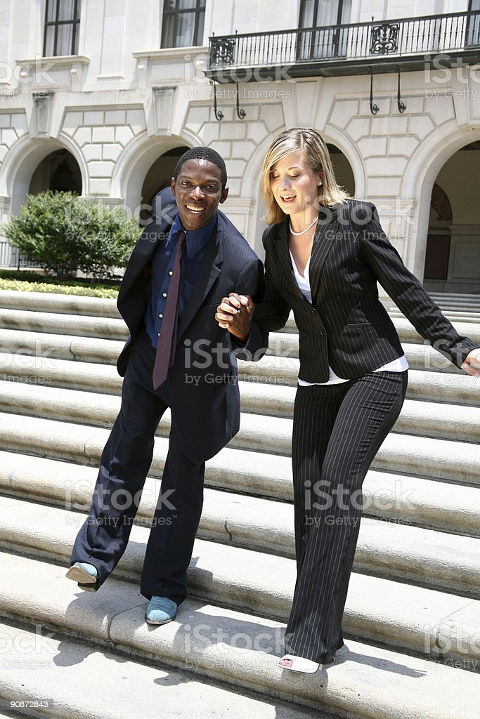 Mixed race couple running down courthouse steps. royalty-free stock photo