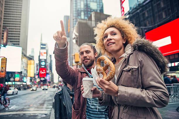 mixed race couple besuchen sie times square in new york im herbst. - sightseeing in new york stock-fotos und bilder
