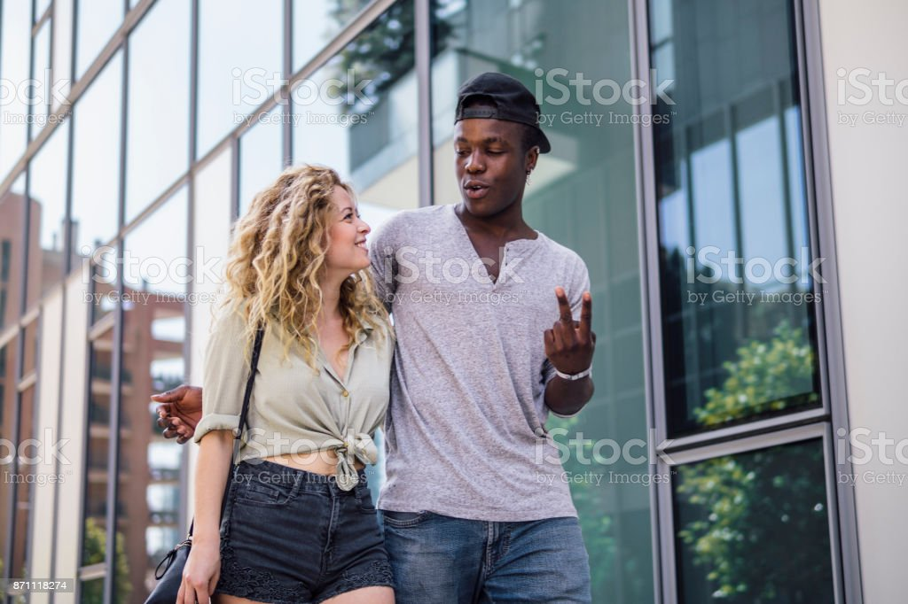 mixed race couple walking in a city - foto stock