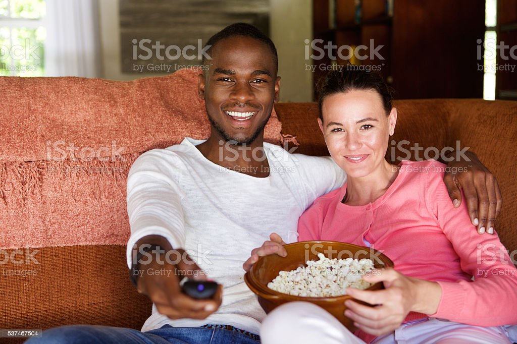 Mixed race couple watching a movie at home stock photo