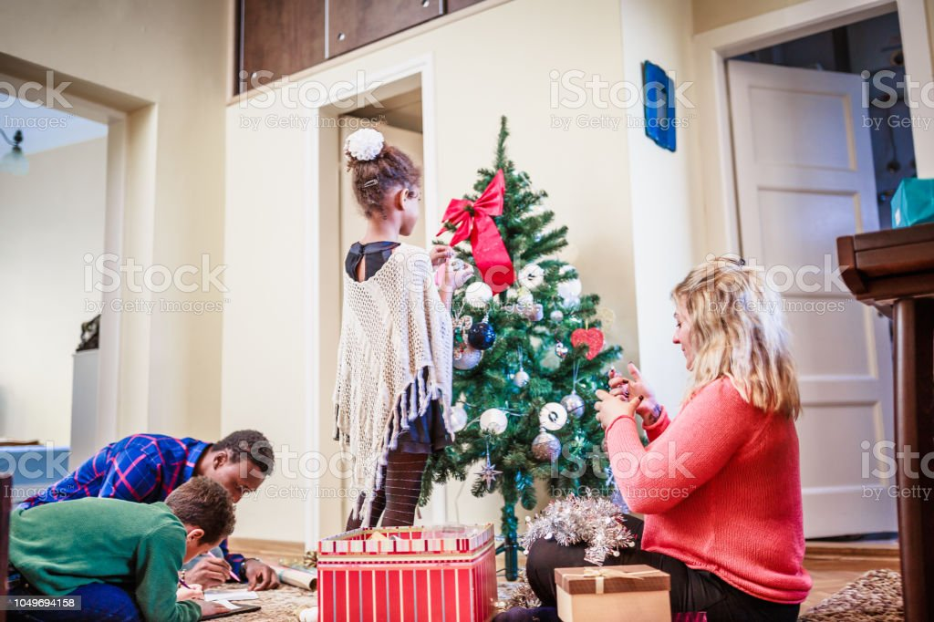 Family moments. Parents with their kids decorating home for Christmas