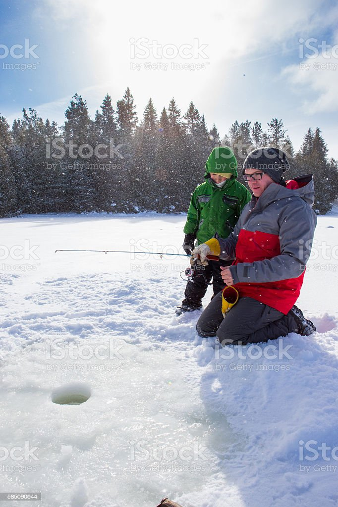 Mixed race family ice fishing stock photo