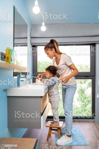 Mixed race family mother helping little daughter to brush teeth at picture id1193200105?b=1&k=6&m=1193200105&s=612x612&h=7bmegn4 umuhdzrhwast8zhjxef rpdm6odtwmgoria=