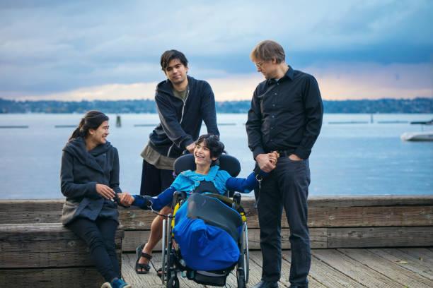 湖で車椅子に障害のある子供を持つ混合人種家族 - disabilitycollection ストックフォトと画像