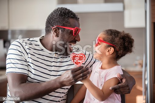 istock Mixed race Father and daughter taste lollipop during Valentine's Day 903926438