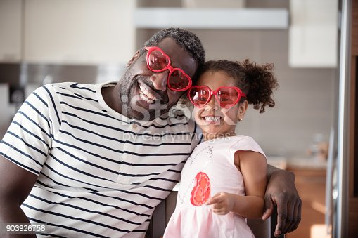 istock Mixed race Father and daughter taste lollipop during Valentine's Day 903926756
