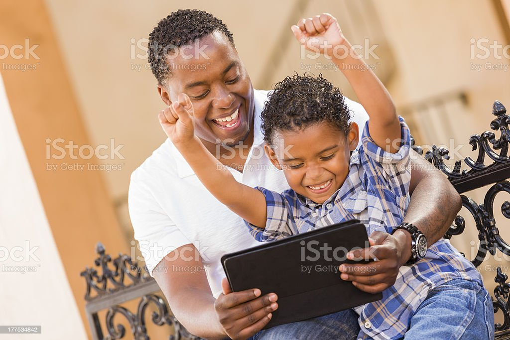 Mixed Race Father and Son Using Touch Pad Computer Tablet royalty-free stock photo