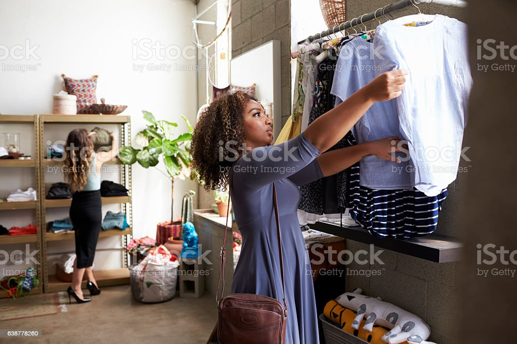 Mixed race female customer clothes shopping in a boutique stock photo