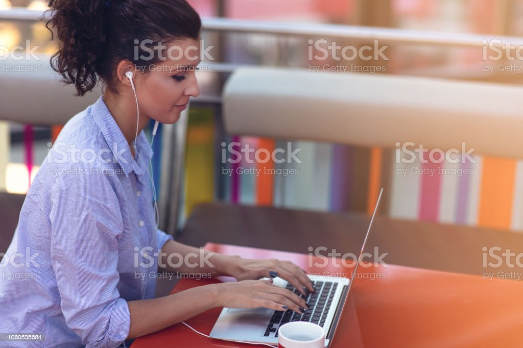 Businesswoman working remotely at cafe with headset and laptop. Mixed...