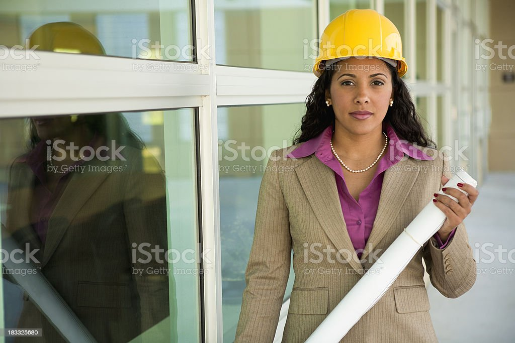Mixed race female with blueprints and hardhat royalty-free stock photo