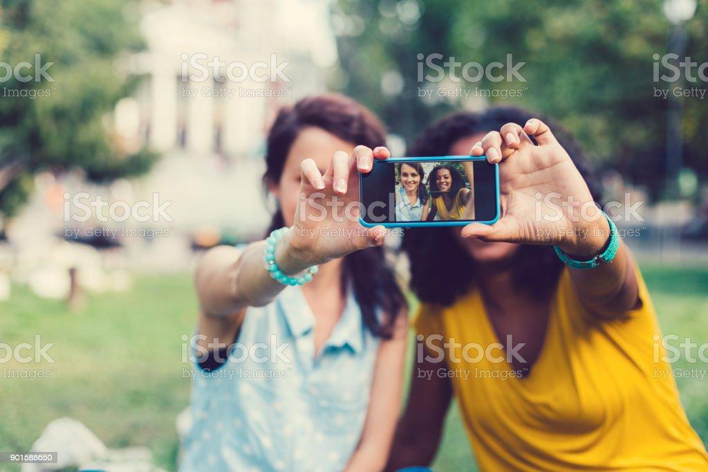 Mixed race friends taking selfie stock photo