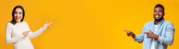 Mixed race girl and black guy pointing at free space Look at this. Excited mixed race girl and black guy pointing at free space over yellow background, panorama excited stock pictures, royalty-free photos & images