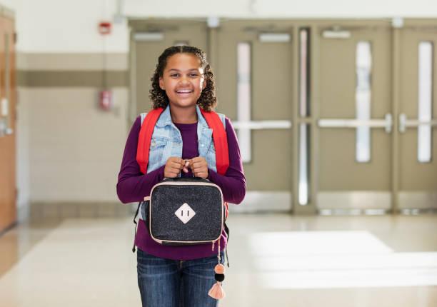 blandad ras flicka i skolan transporterar lunch låda - lunchlåda bildbanksfoton och bilder