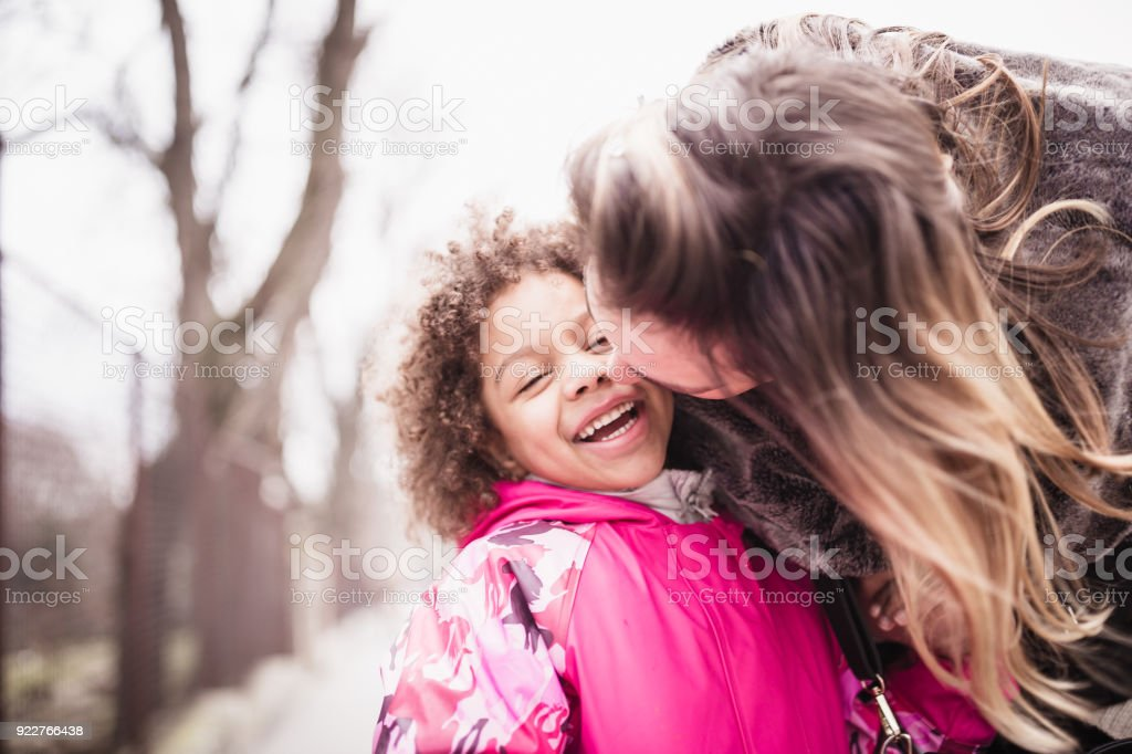 Mixed race girl playing with mother in public park stock photo