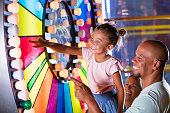 istock Mixed race girl with father at amusement arcade 1307457866