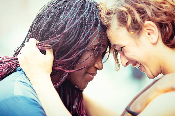 mixed race girlfriends enjoying to stay together - lesbian stock photos and pictures
