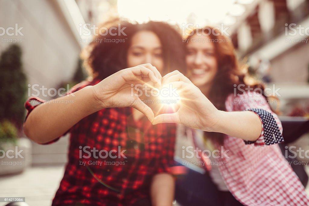 Mixed race girls showing heart shaped hands stock photo